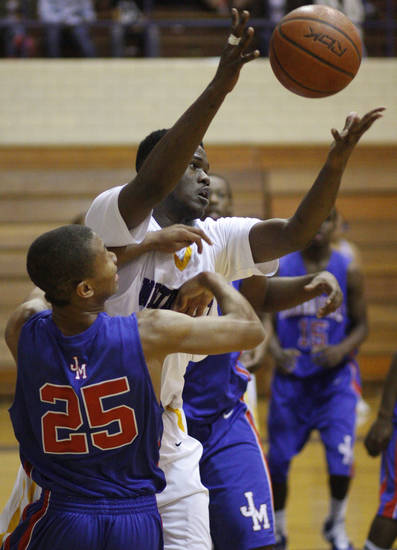 Northwest Classen's Quinton Hardwick reaches for the ball over John Marshall's DeMontrey Mitchell Tuesday night.