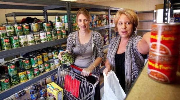 Lisa Wright, a counselor at Putnam City West High School, left,  and Heidi Albrecht, a Department of Human Services school- based social services worker, are shown in the food pantry at Putnam City West High School where students battling hunger can come to get food.  <strong>JIM BECKEL - THE OKLAHOMAN</strong>