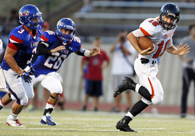 Norman quarterback Zach Long (16) breaks away from Moore's Keoni Walter (26) and Derek Harris (3) on a long touchdown run during a high school football game between Moore and Norman in Moore, Okla., Thursday, Sept. 6, 2012. Photo by Nate Billings, The Oklahoman