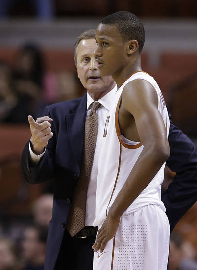 Texas coach Rick Barnes, left, talks with Demarcus Holland during the second half of an NCAA college basketball game against Oklahoma State, Saturday, Feb. 9, 2013, in Austin, Texas. (AP Photo/Eric Gay) ORG XMIT: TXEG111