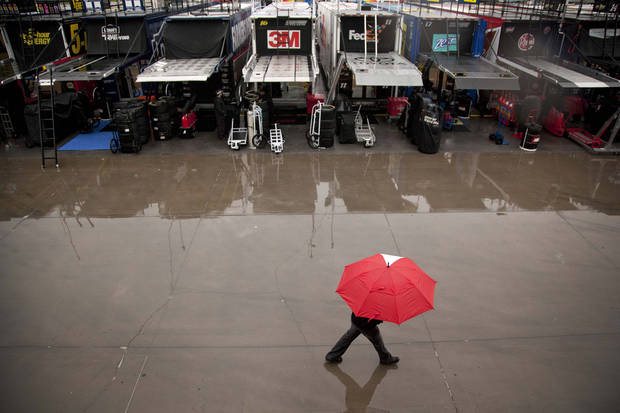 A pit crew worker walks along a row of team trucks outside the Neon Garage during a rain delay at the Las Vegas Motor Speedway, Friday, March 8, 2013 in Las Vegas. Qualifying for the Kobalt 400 NASCAR Sprint Cup Series race was canceled because of rain. (AP Photo/Julie Jacobson)