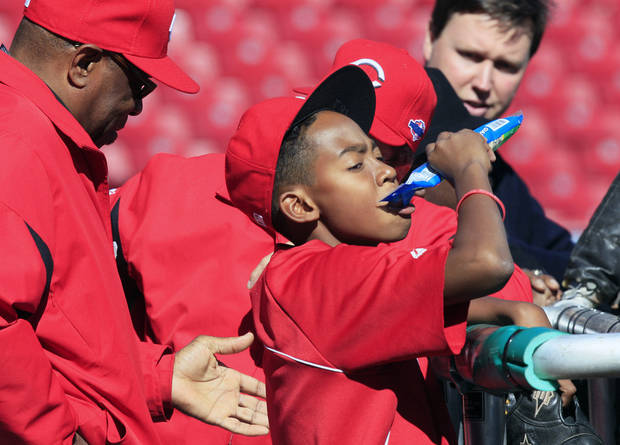 Darren Baker, 13, eats some sunflower seeds while watching batting practice with his father, Cincinnati Reds manager Dusty Baker, left, prior to Game 3 of the National League division baseball series against the San Francisco Giants, Tuesday, Oct. 9, 2012, in Cincinnati. (AP Photo/Al Behrman)