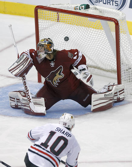 Chicago Blackhawks' Patrick Sharp (10) scores a goal on Phoenix Coyotes goalie Mike Smith during the second period of an NHL hockey game, Sunday, Jan. 20, 2013, in Glendale, Ariz. (AP Photo/Matt York)