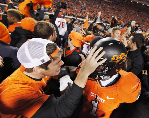 An OSU fan congratulates Joseph Randle (1) on the field after the Bedlam college football game between the Oklahoma State University Cowboys and the University of Oklahoma Sooners at Boone Pickens Stadium in Stillwater, Okla., Saturday, Dec. 3, 2011. OSU beat OU, 44-10. Photo by Nate Billings, The Oklahoman