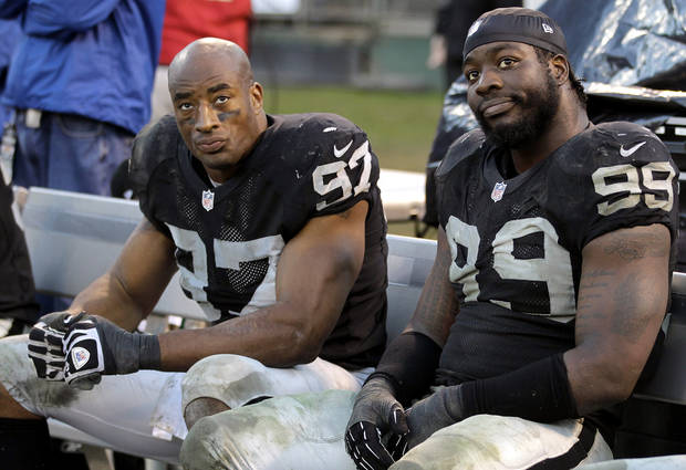 Oakland Raiders defensive end Andre Carter (97) and defensive end Lamarr Houston (99) sit on the bench during the fourth quarter of an NFL football game against the Cleveland Browns in Oakland, Calif., Sunday, Dec. 2, 2012. The Browns won 20-17. (AP Photo/Tony Avelar)