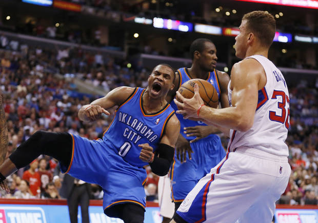 Oklahoma City Thunder guard Russell Westbrook, left, celebrates after dunking the ball over Los Angeles Clippers forward Blake Griffin, right, during the second half of an NBA basketball game in Los Angeles, Wednesday, April 9, 2014. The Thunder won 107-101. (AP Photo/Danny Moloshok)