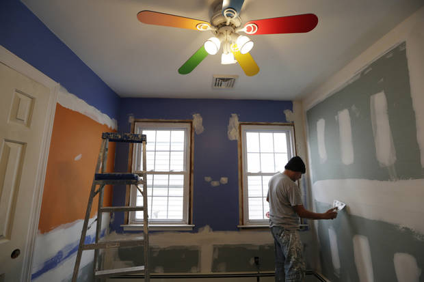 A worker prepares the walls for paint in Ryan and Connor Troy's bedroom in Long Beach, N.Y., Wednesday, Dec. 12, 2012. Renovations to the bungalow style house, severely damaged in Superstorm Sandy, are being paid for by Donald Denihan, who had near-death experiences that convinced him he had a purpose in life, to help others. (AP Photo/Kathy Willens)