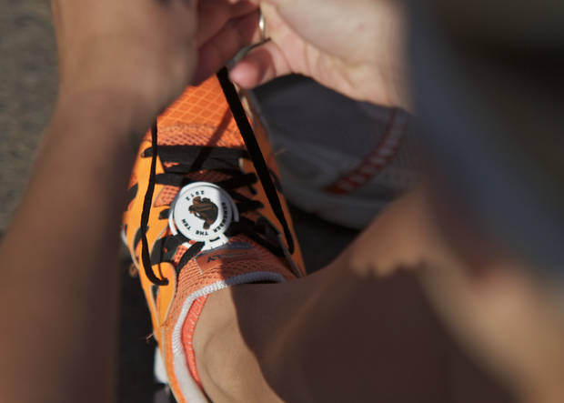 A runner puts the race chip on her shoe before the Remember the Ten run held in Stillwater, Okla., on April 21, 2012. Photo by Mitchell Alcala, for The Oklahoman