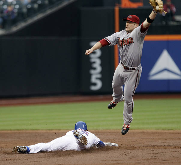 Arizona Diamondbacks second baseman Aaron Hill leaps for the ball thrown by catcher Henry Blanco as New York Mets' Andres Torres steals second base during the third inning of a baseball game Saturday, May 5, 2012, in New York. (AP Photo/Frank Franklin II)