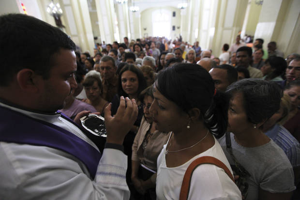 People line up to have ash crosses applied to their foreheads by a Catholic priest during an Ash Wednesday mass in Caracas, Wednesday, Feb. 17, 2010. Ash Wednesday marks the beginning of Lent, a solemn period of 40 days of prayer and self-denial leading up to Easter. (AP Photo/Fernando Llano)