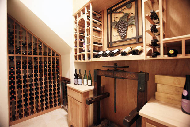 Left: Rick Wolf, working with UBuildIt, designed and installed storage space in the wine closet of his home in Edmond. PHOTO BY PAUL HELLSTERN, THE OKLAHOMAN