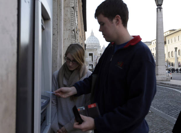 "Ben Kiniry, of Texas, gets cash from an ATM machine along Rome's Via della Conciliazione, the main road leading to the Vatican St. Peter's Basilica, whose dome is visible in background, Thursday, Jan. 3, 2013. It's ""cash only"" now for tourists at the Vatican wanting to pay for museum tickets, souvenirs and other services after Italy's central bank decided to block electronic payments, including credit cards, at the tiny city state. The Italian daily Corriere della Sera reported Thursday that Bank of Italy took the action because the Holy See has not yet fully complied with European Union safeguards against money laundering. That means Italian banks are not authorized to operate within the Vatican, which is in the process of improving its mechanisms to combat laundering. The Vatican says it's scrambling to find a non-Italian bank to provide the electronic payment services ""quite soon"" but declined to discuss Bank of Italy's concerns. The central bank had no immediate comment on the situation. (AP Photo/Alessandra Tarantino)"
