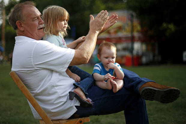 Jerry Mowdy applauds with his grandchildren Yzzy Eddlemon, 2, and Aiden Eddlemon during the Midsummer Nights� Fair.