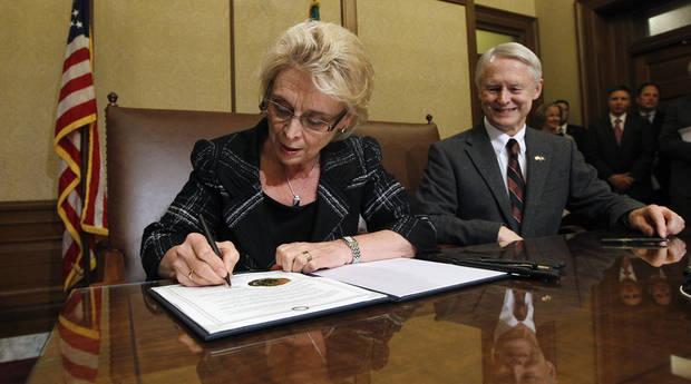 As Secretary of State Sam Reed, right, looks on, Gov. Chris Gregoire signs Referendum 74, a citizen-passed measure that legalizes same-sex marriage in the state, Wednesday, Dec. 5, 2012, in Olympia, Wash. Gregoire and Reed both signed the document at the ceremony, which allows gay couples to marry beginning Dec. 9. (AP Photo/Elaine Thompson)