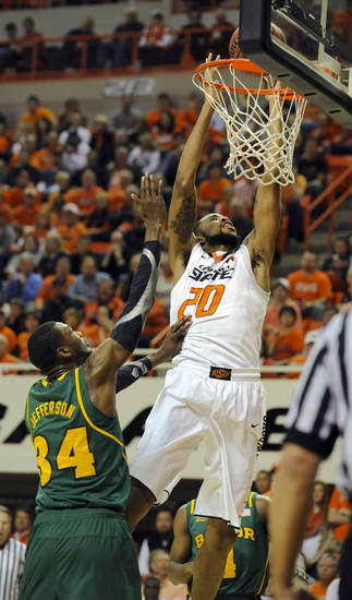 Baylor forward Cory Jefferson, left, watches as Oklahoma State forward Michael Cobbins, dunks the basketball during the second half of an NCAA college basketball game in Stillwater, Okla., Wednesday, Feb. 6, 2013. Cobbins scored nine points in the 69-67 overtime win against Baylor. (AP Photo/Brody Schmidt)