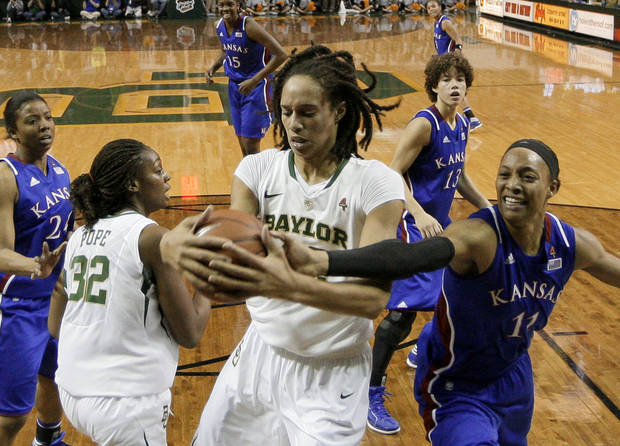 Baylor center Brittney Griner, center, grabs a rebound against Kansas 's Aishah Sutherland (11) in the first half of an NCAA women's college basketball game Saturday, Jan. 28, 2012, in Waco, Texas. Griner had seven rebounds, five blocks and 28-points in the 74-46 Baylor win. (AP Photo/Tony Gutierrez)