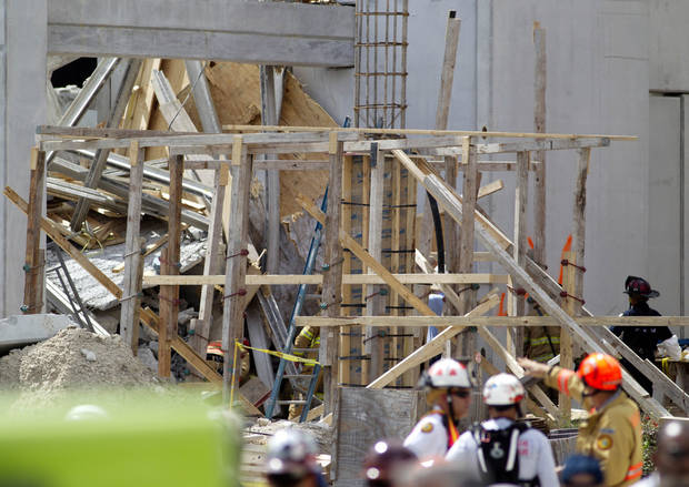 Firefighter look over the rubble after a section of a parking garage under construction at Miami-Dade College in Doral, Fla., collapsed, Wednesday, Oct. 10, 2012 in Doral, killing one worker and trapping at least two others in the rubble, officials said. (AP Photo/J Pat Carter)