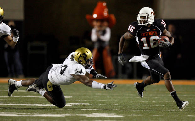 OSU's Perrish Cox returns a punt as Colorado's Marcus Burton (54) misses a tackle during the college football game between Oklahoma State University (OSU) and the University of Colorado (CU) at Boone Pickens Stadium in Stillwater, Okla., Thursday, Nov. 19, 2009. Photo by Sarah Phipps, The Oklahoman
