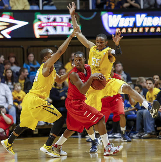 West Virginia's Gary Browne, left, and Keaton Miles (55) defend Radford's Rashun Davis (5) during the second half of an NCAA college basketball game at WVU Coliseum in Morgantown, W.Va., Saturday, Dec. 22, 2012.  West Virginia defeated Radford 72-62. (AP Photo/David Smith)