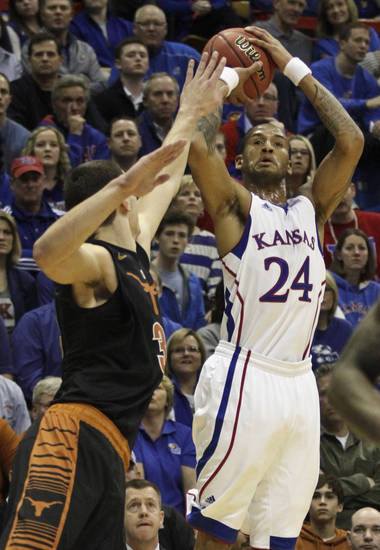 Kansas' Travis Releford (24) shoots over Texas Ioannis Papapetrou during the first half of an NCAA college basketball game on Saturday, Feb. 16, 2013, in Lawrence, Kan. (AP Photo/Ed Zurga)