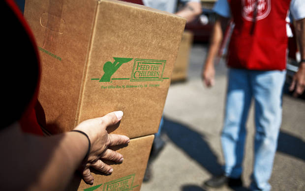Volunteers carry boxes to recipients during a Salvation Army and Feed The Children food distribution to families in Oklahoma City. Photo by Chris Landsberger,  The Oklahoman Archives