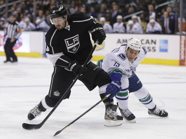 Los Angeles Kings defenseman Drew Doughty, left, shots around Vancouver Canucks left wing Aaron Volpatti during the second period of an NHL Hockey game in Los Angeles, Monday, Jan. 28, 2013. (AP Photo/Chris Carlson)