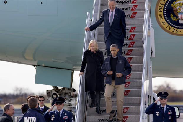 <p>President Barack Obama, followed by Sen. Kirsten Gillibrand, D-N.Y, and Sen. Charles Schumer, D-N.Y., arrive at JFK International Airport in New York, Thursday, Nov. 15, 2012, before being greeted by New York City Mayor Michael Bloomberg, left, Housing and Urban Development Secretary Shaun Donovan, in HUD jacket, and other state, local and federal officials, before taking an aerial tour of damage along the New York coastline in the wake of Superstorm Sandy. (AP Photo/Craig Ruttle)</p>