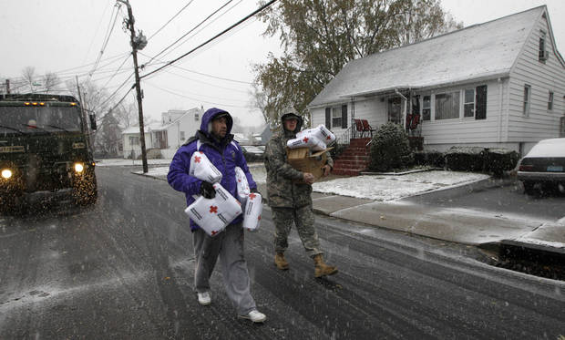 Volunteer Chris Braitsch, left, and National Guardsman Brandon Kyle distribute blankets to residents of Little Ferry, N.J., as a Noreaster approached in the wake of Superstorm Sandy, Wednesday, Nov. 7, 2012. (AP Photo/Kathy Willens) ORG XMIT: NYKW102