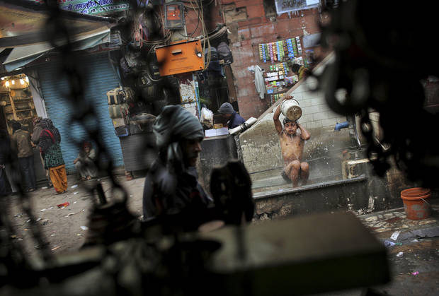An Indian man washes himself at an outdoor basin on a cold morning in New Delhi, India, Monday, Jan. 7, 2013. North India continues to face below average weather conditions with dense fog affecting flights and trains. More than 100 people have died of exposure as northern India deals with historically cold temperatures. (AP Photo/Kevin Frayer)