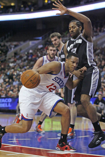 San Antonio Spurs' Kawhi Leonard defends as Philadelphia 76ers' Evan Turner (12) drives into the lane in the first half of an NBA basketball game Monday, Jan. 21, 2013, in Philadelphia. (AP Photo H. Rumph Jr)
