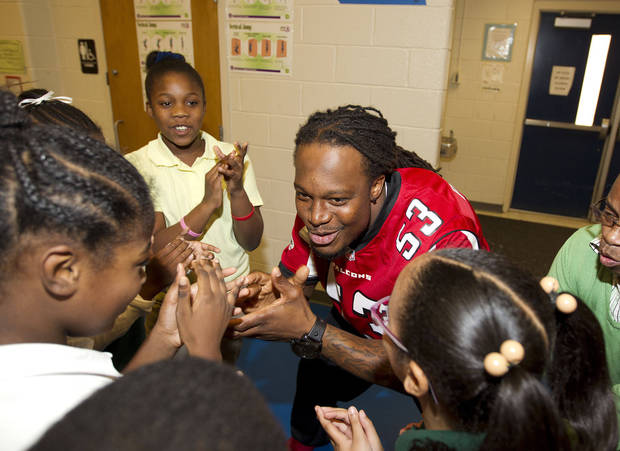Atlanta Falcons linebacker Mike Peterson (53) plays with kids at Clifton elementary School in Atlanta, Tuesday, Oct. 9, 2012. Peterson was one of several Falcons players who spent the morning visiting Atlanta-area schools to stress the importance of exercise as part of the NFL's Hometown Huddle program. (AP (AP Photo/John Bazemore)