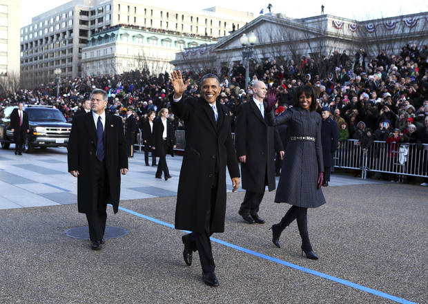 President Barack Obama and first lady Michelle Obama wave as they walk down Pennsylvania Avenue in Washington, Monday, Jan. 21, 2013, during the Inaugural Parade after his ceremonial swearing-in on Capitol Hill during the 57th Presidential Inauguration. (AP Photo/The New York Times, Doug Mills, Pool) ORG XMIT: NYNYT306