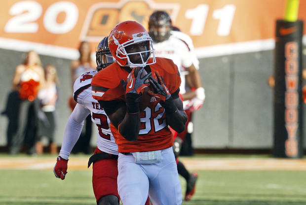 Oklahoma State wide receiver Isaiah Anderson (82) catches a pass from quarterback Clint Chelf in front of Texas Tech defensive back Bruce Jones (24) and takes it in for a touchdown in the second quarter of an NCAA college football game in Stillwater, Okla., Saturday, Nov. 17, 2012. (AP Photo/Sue Ogrocki)