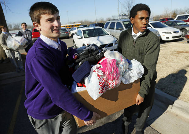 "Mount St. Mary boys basketball players Collin Adney and D.J. Lloyd carry donated items to a truck at Sacred Heart Catholic Church, 2706 S Shartel, before the 2013 ""Hoops 4 Hope"" Catholic high school basketball tournament on Friday in Oklahoma City. Photo by Nate Billings, The Oklahoman <strong>NATE BILLINGS</strong>"