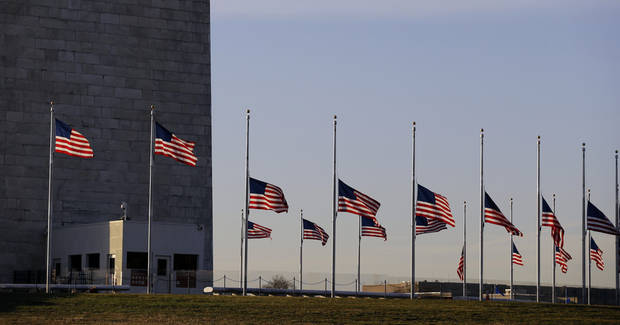American flags surrounding the Washington Monument in Washington are lowered to half-staff in a mark of respect for the victims on the Connecticut elementary school shootings, Friday, Dec. 14, 2012. (AP Photo/Alex Brandon) ORG XMIT: DCAB103