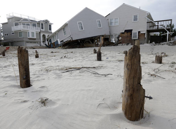 A house that broke from its piers, front, during Superstorm Sandy rests against a neighboring house on Long Beach Island, N.J., Friday, Nov. 2, 2012. Sandy, the storm that made landfall Monday, caused multiple fatalities, halted mass transit and cut power to more than 6 million homes and businesses.(AP Photo/Patrick Semansky) ORG XMIT: NJPS111