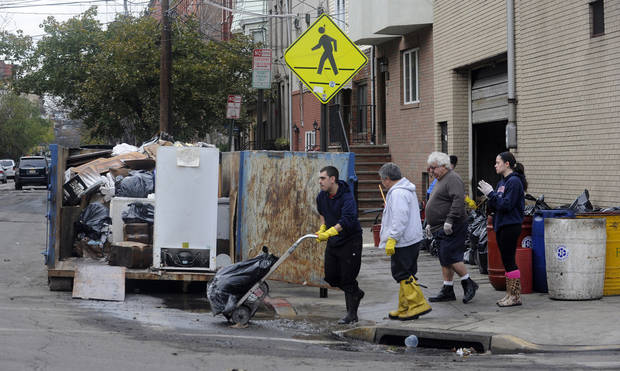 <p>Residents on Adams Street fill a dumpster with belongings from an apartment building were ruined by the floodwaters from Superstorm Sandy, Thursday Nov. 1, 2012 in Hoboken, N.J. (AP Photo/Joe Epstein)</p>