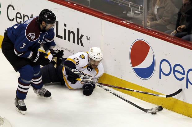 Colorado Avalanche defenseman Ryan O'Byrne, left, battles for control of the puck with Nashville Predators center Paul Gaustad in the first period of an NHL hockey game in Denver, Saturday, March 30, 2013. (AP Photo/David Zalubowski)