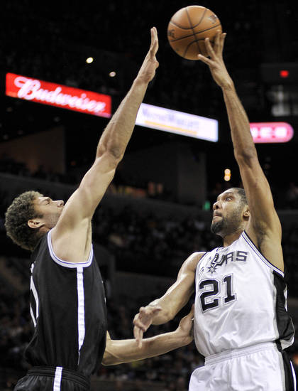 San Antonio Spurs' Tim Duncan, right, shoots over Brooklyn Nets' Brook Lopez during the first half of an NBA basketball game, Monday, Dec. 31, 2012, in San Antonio. (AP Photo/Darren Abate)