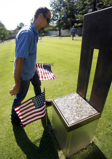 James Sing of Midwest City places flags next to each of the chair monuments at the Oklahoma City bombing memorial on Monday, July 1, 2013. Photo by Aliki Dyer/The Oklahoman