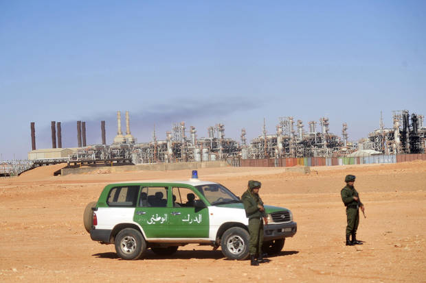 FILE - This  Jan. 31, 2013, file photo shows Algerian soldiers standing guard during a visit for news media organized by the Algerian authorities at the gas plant in Ain Amenas, seen on background. New corruption scandals are shining a fresh spotlight on Sonatrach, which jointly with BP and Norway�s Statoil runs the desert gas plant that was the scene of a bloody hostage standoff last month. (AP Photo/File)