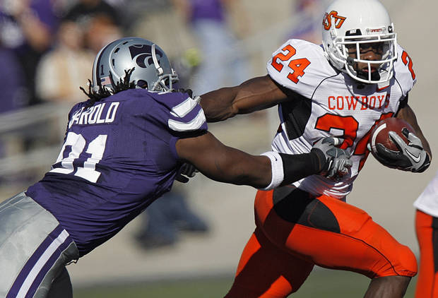 Oklahoma State's Kendall Hunter (24) runs past Kansas State's Brandon Harold (91) during the first half of the college football game between the Oklahoma State University Cowboys (OSU) and the Kansas State University Wildcats (KSU) on Saturday, Oct. 30, 2010, in Manhattan, Kan.   Photo by Chris Landsberger, The Oklahoman