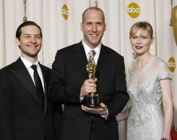 """Actors Tobey Maguire, left, and Kirsten Dunst, right, stand with writer Michael Arndt as he poses with the Oscar he won for best original screenplay for his work on """"Little Miss Sunshine"""" at the 79th Academy Awards Sunday, Feb. 25, 2007, in Los Angeles. (AP file)"""
