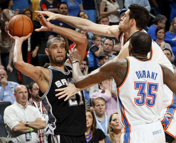San Antonio's Tim Duncan (21) tries to pass the ball away from Oklahoma City's Nick Collison (4) and Kevin Durant (35) during the NBA basketball game between the Oklahoma City Thunder and the San Antonio Spurs at Chesapeake Energy Arena in Oklahoma City, Friday, March 16, 2012. San Antonio won, 114-105. Photo by Nate Billings, The Oklahoman