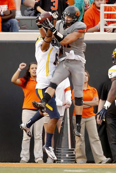 Oklahoma State&#039;s Charlie Moore (17)  catches a touchdown in the third quarter during a college football game between Oklahoma State University (OSU) and the West Virginia University at Boone Pickens Stadium in Stillwater, Okla., Saturday, Nov. 10, 2012. Photo by Sarah Phipps, The Oklahoman