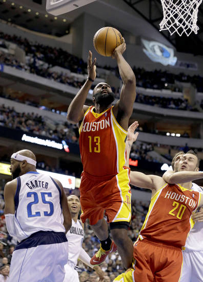 Houston Rockets' James Harden (13) is fouled going to the basket between Dallas Mavericks' Vince Carter (25) and Rockets' Donatas Motiejunas (20), of Lithuania, in the first half of an NBA basketball game, Wednesday, March 6, 2013, in Dallas. (AP Photo/Tony Gutierrez)