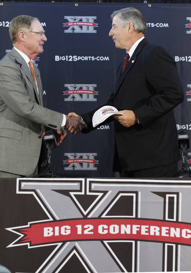 New Big 12 Commissioner Bob Bowlsby, right, and shakes hands with Oklahoma State University President Burns Hargis at the news conference introducing Bowlsby to the media at Big 12 headquarters  Friday, May 4, 2012, in Irving, Texas.  (AP Photo/LM Otero) ORG XMIT: TXMO105