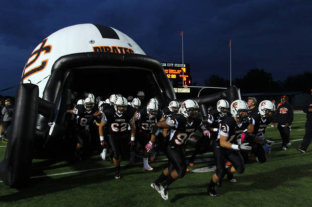 The Putnam City Pirates take the field before the Putnam City - Broken Arrow high school football game at Putnam City Stadium Friday night. PHOTO BY HUGH SCOTT FOR THE OKLAHOMAN ORG XMIT: KOD