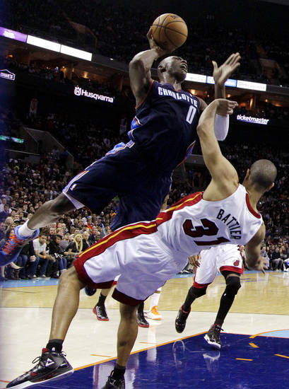 Charlotte Bobcats' Bismack Biyombo (0) runs into Miami Heat's Shane Battier (31) as he drives to the basket during the second half of an NBA basketball game in Charlotte, N.C., Wednesday, Dec. 26, 2012. Biyombo was called for a foul. Miami won 105-92. (AP Photo/Chuck Burton)