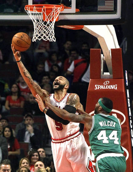 Boston Celtics forward Chris Wilcox (44) fouls Chicago Bulls forward Carlos Boozer during the first half of an NBA basketball game, Monday, Nov. 12, 2012, in Chicago. (AP Photo/Charles Rex Arbogast)